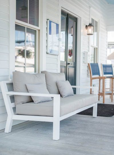 White bench decorated with pillows on a veranda