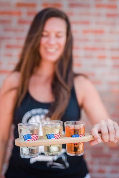 Woman holding three shot glasses at Cider Tasting