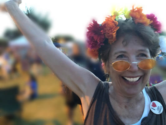 Smiling woman wearing a flower wreath and sunglasses, dancing at Lovefest