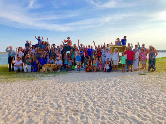Group photo of volunteers at love sign at the beach