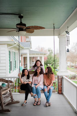Women sitting on a porch swing and smiling to each other